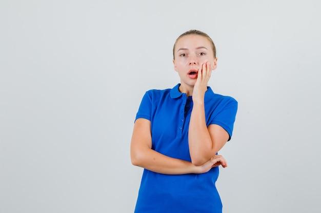 Junge dame, die hand auf wange im blauen t-shirt hält und überrascht schaut