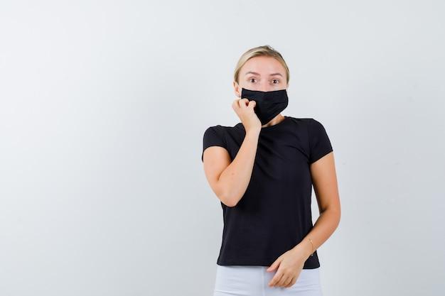 Junge dame, die hand auf wange im schwarzen t-shirt, in der maske hält und erstaunt schaut, vorderansicht.