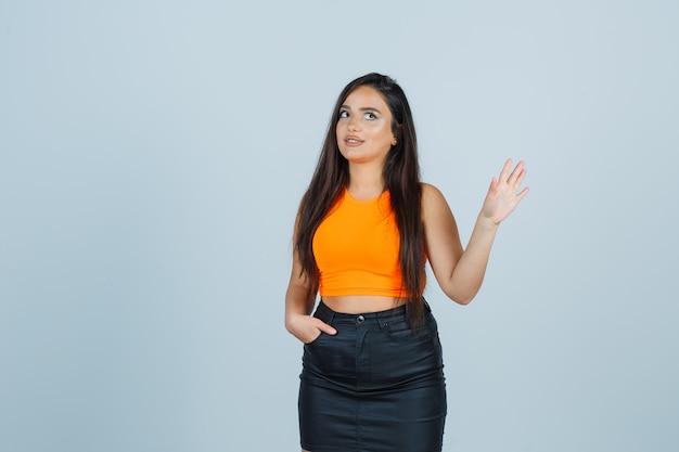 Junge dame, die hand in der tasche hält, während handfläche im unterhemd, im minirock zeigt und selbstbewusst aussieht. vorderansicht.