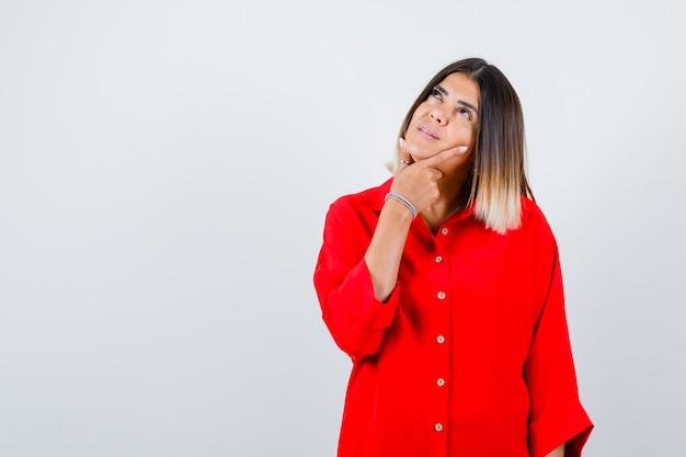 Junge dame, die hand unter kinn im roten übergroßen hemd hält und nachdenkliche vorderansicht schaut.