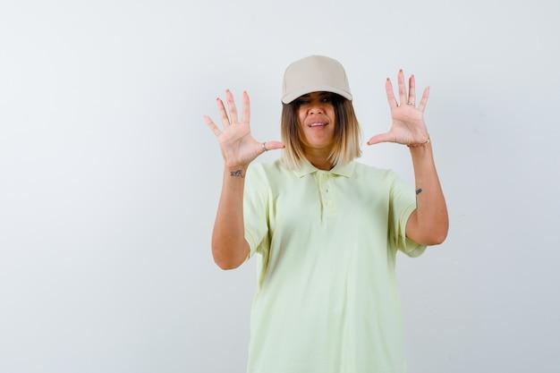 Junge dame, die handflächen in übergabegeste im t-shirt, in der mütze und im hilflosen blick von vorne zeigt.