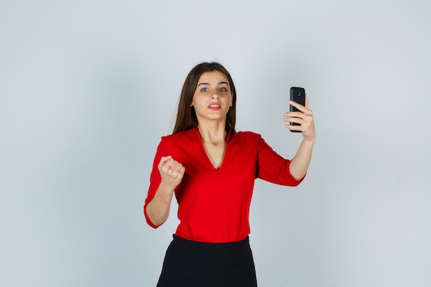 Junge dame, die handy hält, während faust in roter bluse erhöht
