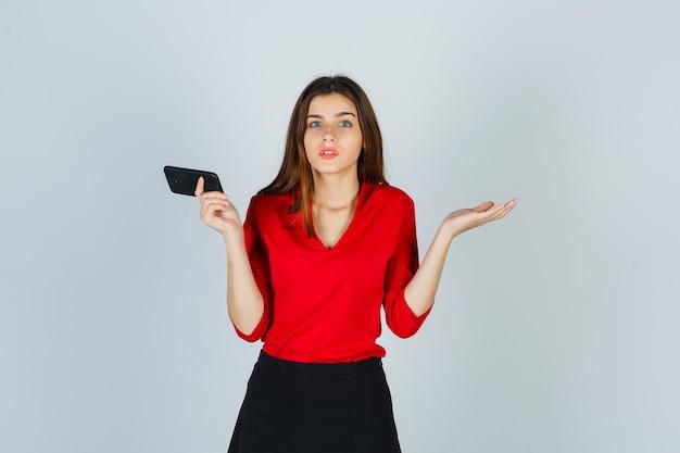 Junge dame, die handy hält, während sie hilflose geste in roter bluse zeigt