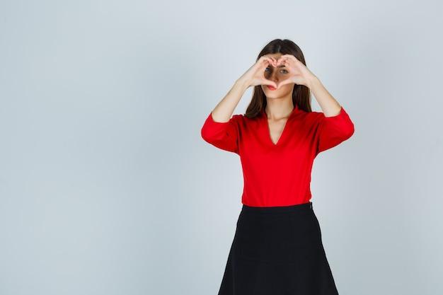 Junge dame, die herzgeste in der roten bluse, im schwarzen rock zeigt und niedlich schaut