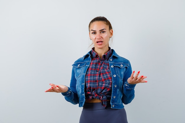 Junge dame, die hilflose geste im hemd, in der jacke zeigt und verwirrt schaut. vorderansicht.