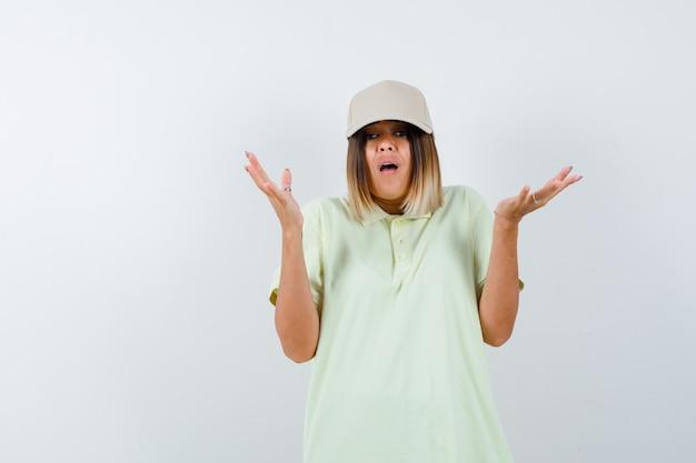 Junge dame, die hilflose geste im t-shirt, in der mütze zeigt und gestresst aussieht. vorderansicht.