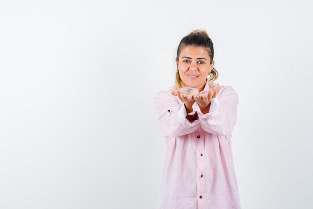 Junge dame, die hohlen hände im rosa hemd streckt und fröhlich aussieht