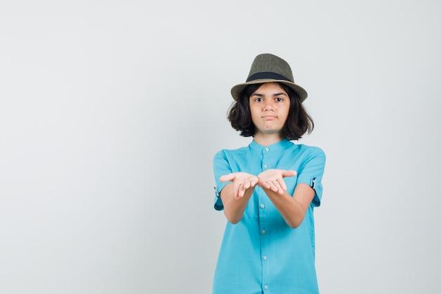 Junge dame, die ihre hände mit offenen handflächen im blauen hemd, hut zeigt