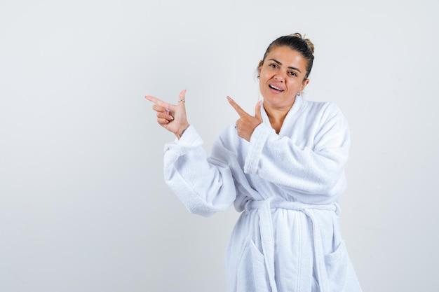 Junge dame, die im bademantel auf die obere linke ecke zeigt und selbstbewusst aussieht