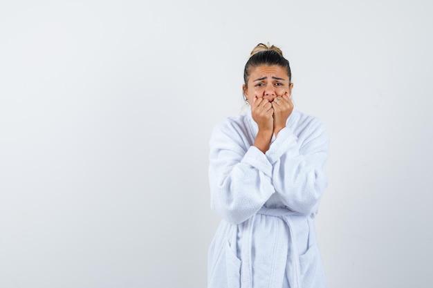 Junge dame, die im bademantel den mund mit fäusten bedeckt und verwirrt aussieht