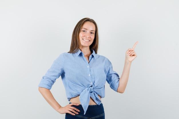 Junge dame, die im blauen hemd, in der hose oben zeigt und freudig aussieht.