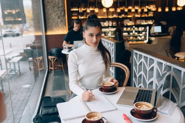 Junge dame, die im café im internet surft