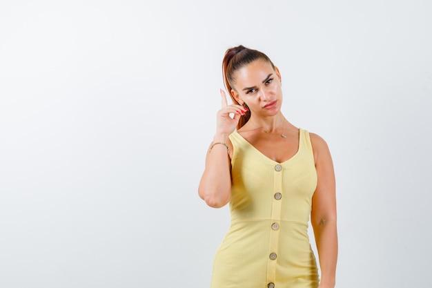 Junge dame, die im gelben kleid zeigt und nachdenklich, vorderansicht schaut.