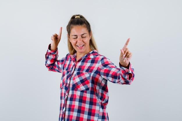 Junge dame, die im karierten hemd nach oben zeigt und verspielte vorderansicht sieht.