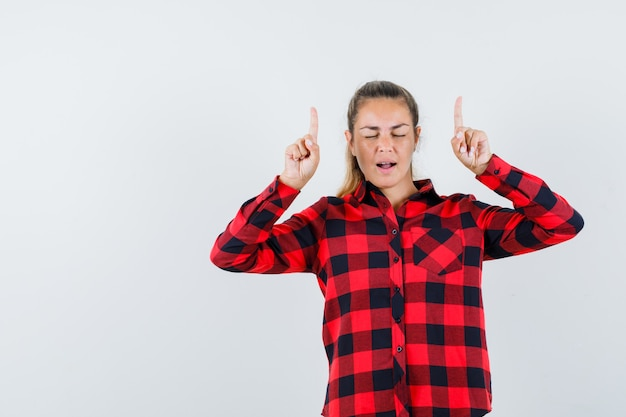 Junge dame, die im karierten hemd zeigt und selbstbewusst aussieht