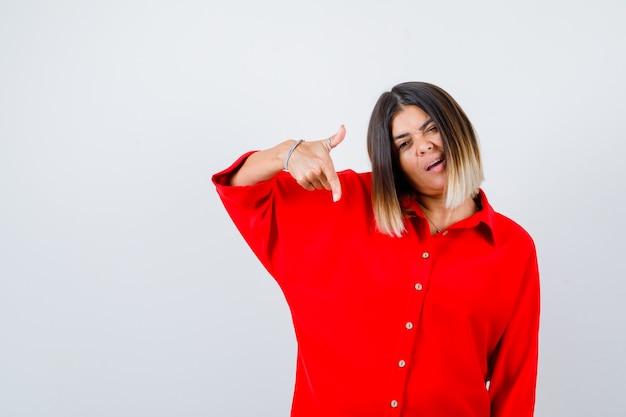 Junge dame, die im roten oversize-hemd nach unten zeigt und selbstbewusst aussieht. vorderansicht.