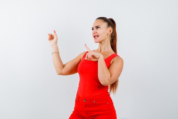 Junge dame, die im roten unterhemd, in der roten hose beiseite zeigt und fröhlich sieht, vorderansicht.