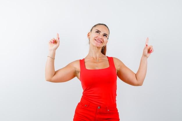 Junge dame, die im roten unterhemd, in der roten hose oben zeigt und fröhlich aussieht. vorderansicht.