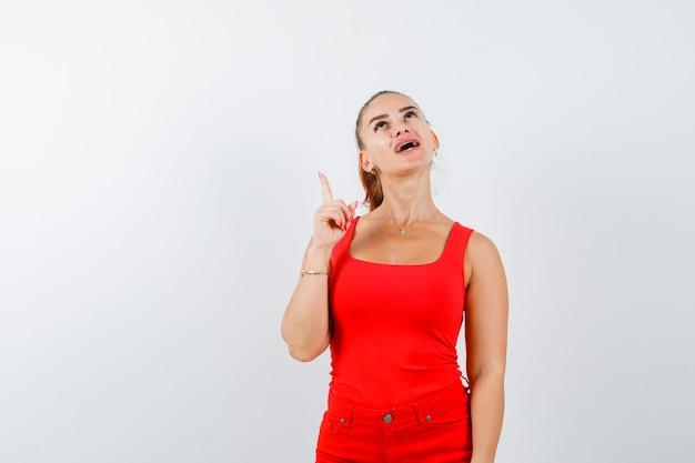 Junge dame, die im roten unterhemd, in der roten hose oben zeigt und fröhlich sieht, vorderansicht.