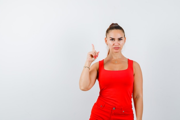 Junge dame, die im roten unterhemd, in der roten hose oben zeigt und selbstbewusst aussieht, vorderansicht.
