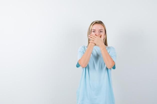 Junge dame, die im t-shirt die hände vor dem mund hält und verängstigt aussieht
