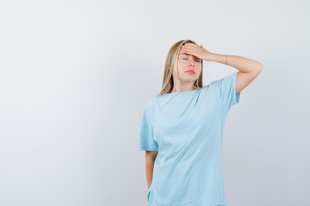 Junge dame, die im t-shirt die hand auf die stirn hält und erschöpft aussieht, isoliert