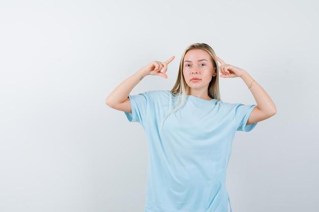 Junge dame, die im t-shirt nach oben zeigt und selbstbewusst aussieht