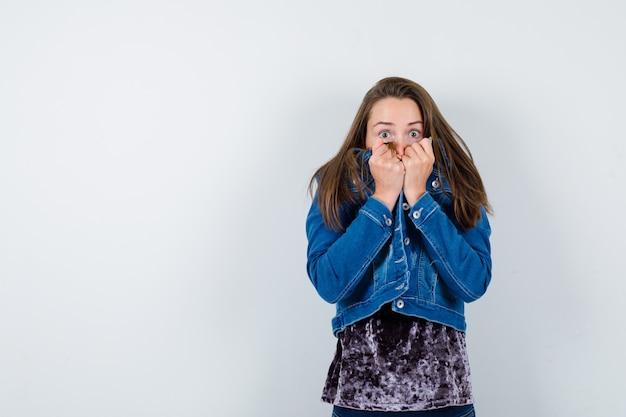Junge dame, die in ängstlicher pose in bluse, jeansjacke steht und verängstigt aussieht. vorderansicht.