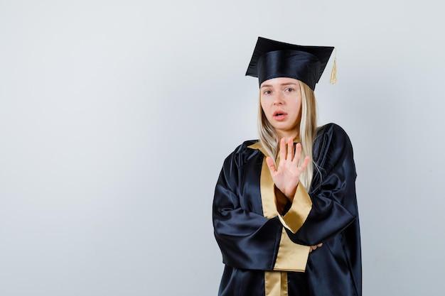 Junge dame, die in akademischer kleidung eine stopp-geste zeigt und verängstigt aussieht