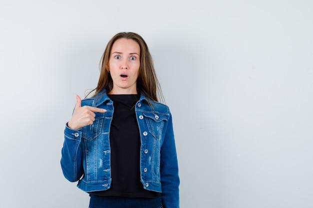 Junge dame, die in bluse, jacke und verwirrt auf sich selbst zeigt, vorderansicht.