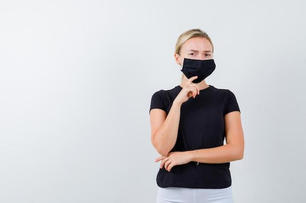Junge dame, die in denkender pose in t-shirt, hose, medizinischer maske steht und zögerlich aussieht