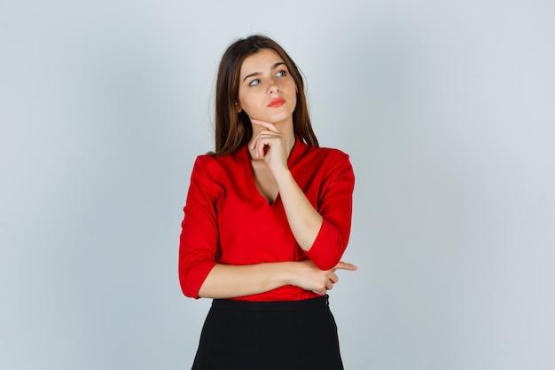 Junge dame, die in der denkenden haltung in der roten bluse, im rock steht und nachdenklich schaut