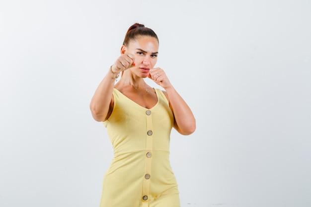 Junge dame, die in der kampfhaltung im gelben kleid steht und zuversichtlich schaut. vorderansicht.