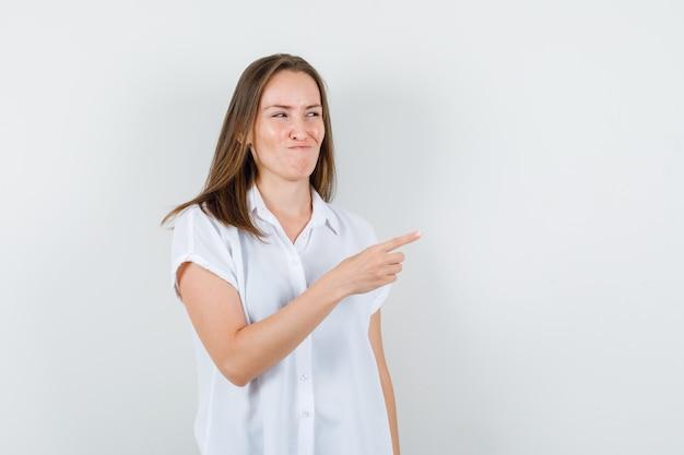 Junge dame, die in der weißen bluse beiseite zeigt und spöttisch aussieht