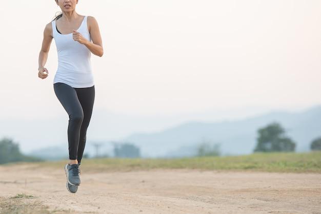 Junge dame, die in einem gesunden lebensstil beim joggen entlang einer landstraße genießt