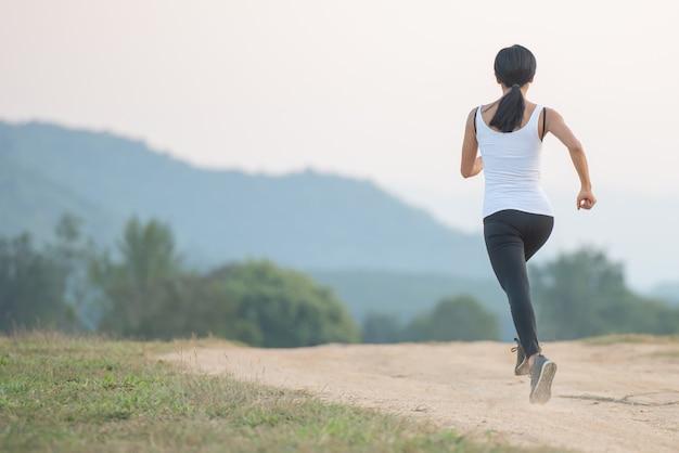 Junge dame, die in einem gesunden lebensstil genießt, während sie entlang einer landstraße, übung und fitness und training im freien joggt.