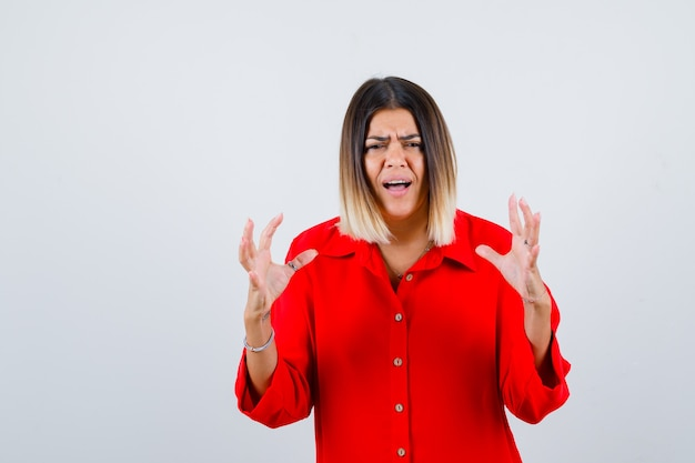 Junge dame, die in einem roten übergroßen hemd auf aggressive weise die hände hält und genervt aussieht. vorderansicht.
