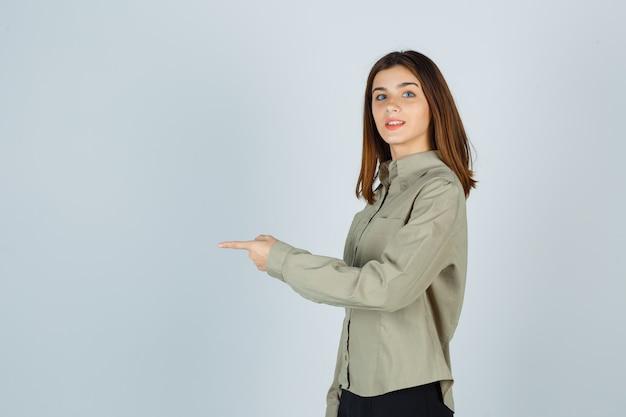 Junge dame, die in hemd, rock geradeaus zeigt und fröhlich aussieht.