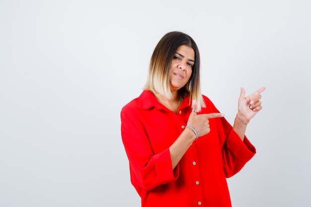 Junge dame, die in rotem übergroßem hemd beiseite zeigt und erfreut aussieht, vorderansicht.