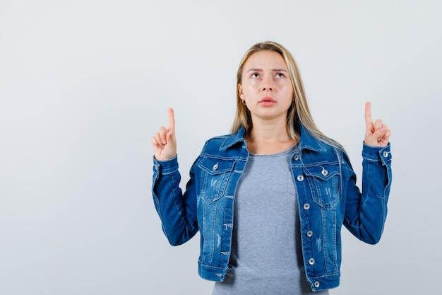 Junge dame, die in t-shirt, jeansjacke, rock nach oben zeigt und nachdenklich aussieht.