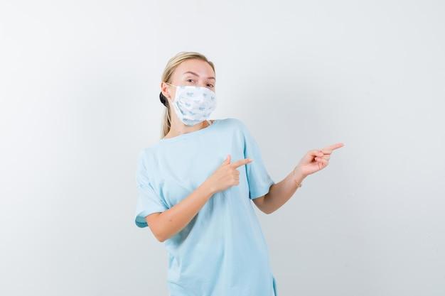 Junge dame, die in t-shirt, maske und fröhlichem gesicht auf die rechte seite zeigt Kostenlose Fotos
