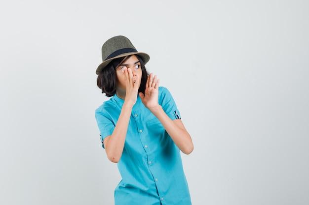 Junge dame, die jemanden mit lauter stimme im blauen hemd anruft und vorsichtig schaut