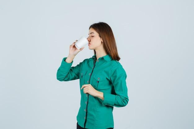 Junge dame, die kaffee vom plastikbecher im hemd trinkt und konzentriert schaut. vorderansicht.