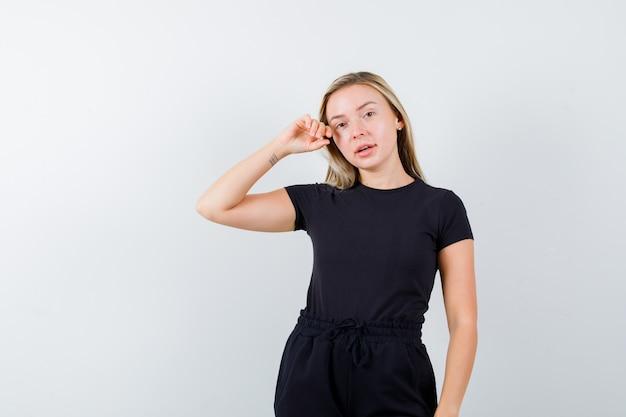 Junge dame, die kamera betrachtet, während sie im t-shirt, in der hose und im verführerischen blick aufwirft. vorderansicht.