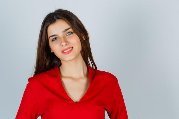 Junge dame, die kamera in der roten bluse betrachtet und verführerisch schaut