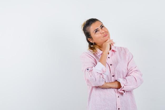 Junge dame, die kinn auf hand im rosa hemd stützt und verträumt aussieht