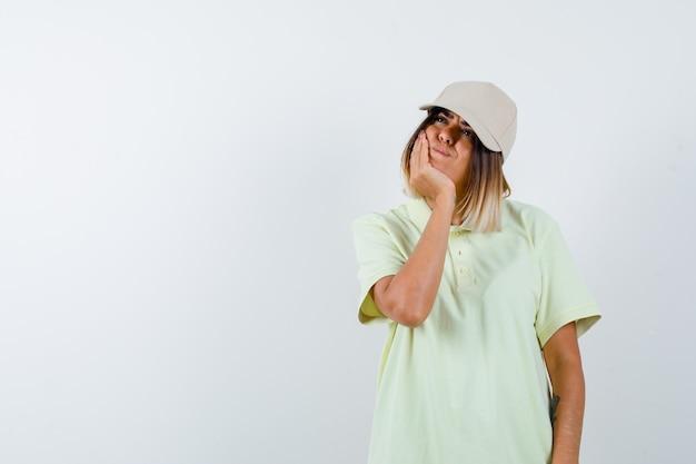 Junge dame, die kinn auf hand in t-shirt, mütze und nachdenklich aussehend, vorderansicht lehnt.
