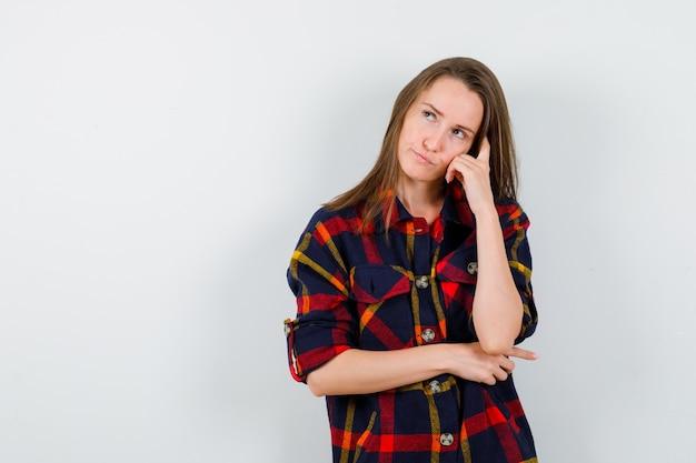 Junge dame, die kopf auf hand im freizeithemd lehnt und nachdenklich, vorderansicht schaut.