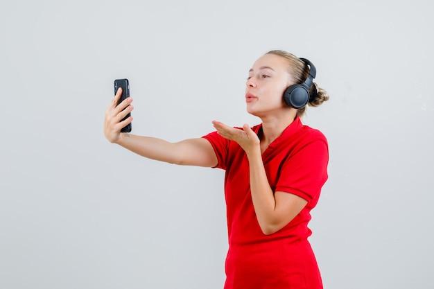 Junge dame, die luftkuss auf videoanruf im roten t-shirt und in den kopfhörern sendet