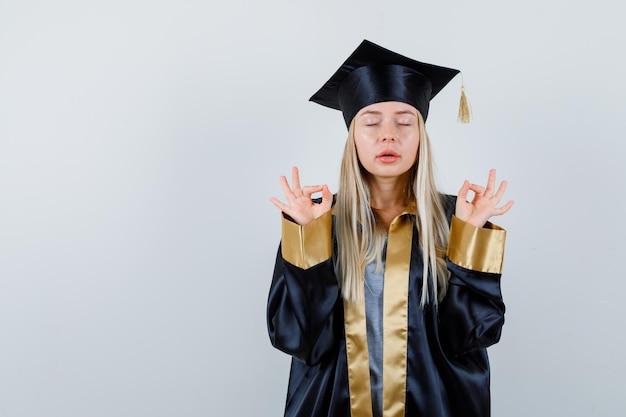 Junge dame, die meditationsgeste in akademischer kleidung zeigt und friedlich aussieht